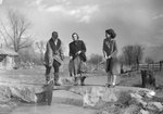 Three women fishing from a small bridge, one pulling a rather large fish out of the water