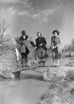 Three women fishing from a small bridge