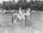 Broadway Horse Show, a woman leading a pony, which a young girl is riding by William Garber