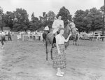 Broadway Horse Show, a woman leading a horse, which another woman holding a trophy is riding by William Garber