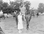 Broadway Horse Show, a man posing on a horse with a trophy in his hand, a woman standing next to him