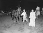 Broadway Horse Show, a man holding a trophy and leading a horse, with a woman walking next to him
