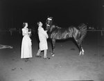 Broadway Horse Show, side view of a man and woman approaching a horse
