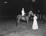 Broadway Horse Show, woman on a horse and holding a trophy, with another woman standing close by