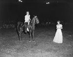 Broadway Horse Show, woman on a horse and holding a ribbon, with another woman standing nearby