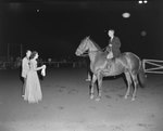 Broadway Horse Show, a man riding a horse towards a woman holding a ribbon