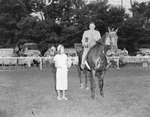 Broadway Horse Show, a man posing on a horse and holding a trophy, with a woman standing beside him