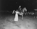 Broadway Horse Show, a woman on a horse holding a trophy, with another woman standing beside her