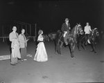 Broadway Horse Show, a man and woman riding on separate horses with spectators in the background