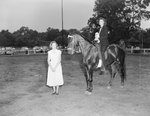 Broadway Horse Show, a woman riding a horse holding a ribbon and another woman standing close by