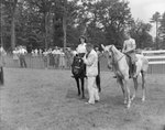 A woman and a young boy riding separate horses side by side, with spectators in the background