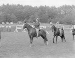 Men on horseback, riding in a single file line