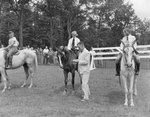 Three young people on horseback, with a man attaching ribbons to their horses