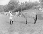 Side view of a woman standing face to face with a horse, its reins in her hands