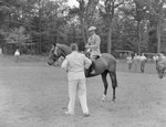 A man riding a horse with a ribbon attached to its bridle, and another man standing in the foreground with his back to the camera