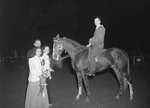Timberville Horse Show, side view of a man on a horse that has won a ribbon, with two women and a man standing nearby