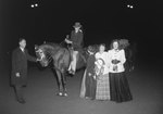 Timberville Horse Show, a man holding a trophy riding a horse with a ribbon. Three women stand nearby, and a man stands at the horse's head