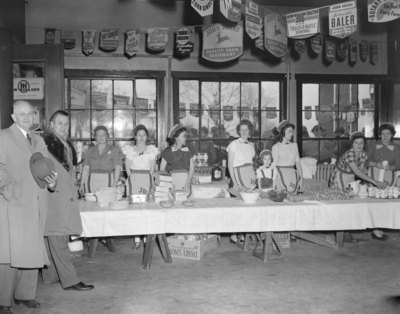 """John Deere Day,"" a number of women standing behind a long table of refreshements"