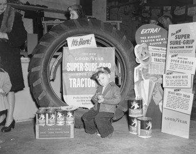 """John Deere Day,"" a small boy sitting in front of a large tractor tire display"