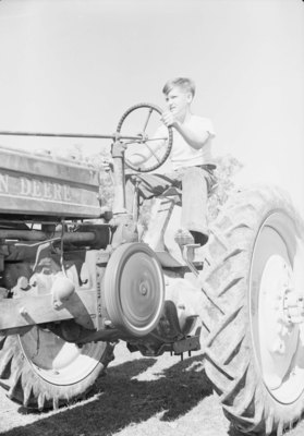 """John Deere Day,"" close up view of a young boy sitting on or driving a John Deere tractor"