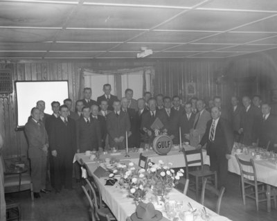 A large group of men wearing suits posing at a banquet of sorts hosted by the Gulf company