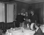 Three men in suits conversing at the head of the table at a banquet hosted by the Gulf company