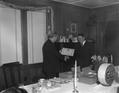 "A man presenting another man with a plaque at the head of the table at a banquet hosted by the Gulf company. Plaque reads, ""To Joseph Rhodes in recognition an appreciation of our business association which began in 1933."""