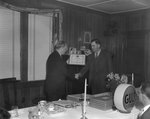 "A man presenting another man with a plaque at the head of the table at a banquet hosted by the Gulf company. Plaque reads, ""To Joseph Rhodes in recognition an appreciation of our business association which began in 1933."" by William Gaber"