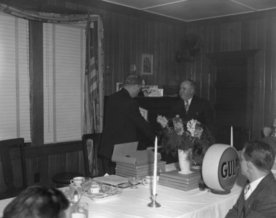 Two men in suits shaking hands at the head of the banquet table, hosted by Gulf