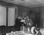 "A man presenting another man with a plaque at the head of the table at a banquet hosted by the Gulf company. Plaque reads ""To H.E. Estep in recognition and appreciation of our business association which began in 1929."" by William Gaber"