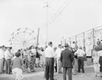 Crowds of people at the Shenandoah County Fair, with a ferris wheel in the background
