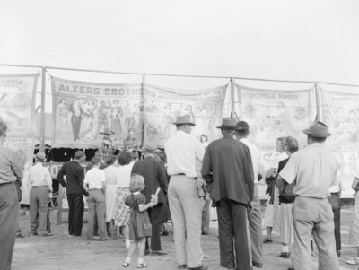 "Crowds of people at the Shenandoah County Fair, with banners advertising the ""Alters Brothers United Assembly of the World's Strangest People"""