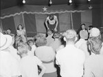 Crowds of people at the Shenandoah County Fair, watching a man on stage with enlarged ribs by William Gaber