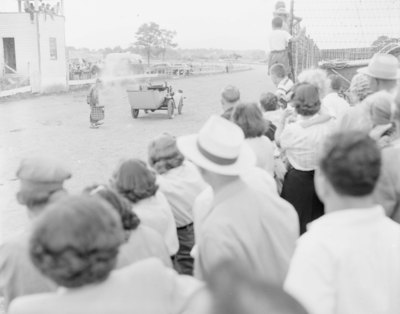 Crowds of people at the Shenandoah County Fair watching over the fence as an elderly man walks towards what seems to be a very old automobile