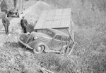 An automobile stuck in a large ditch with a small shed or other structure. VA License plate 64-512 by William Garber
