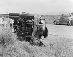 Front view of an automobile laying on its side at the edge of a road