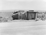An automobile laying on its side, with the top of the vehicle pictured by William Garber