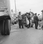A number of men standing next to an automobile that is laying on its side; the wheels of a tractor-trailer are pictured in the foreground.