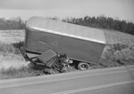 Alternate view of a tractor-trailer after a serious accident, mangled in a ditch off the side of the road