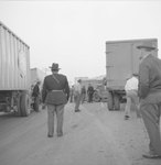 A large number of men walking through and examining the tractor-trailer accident