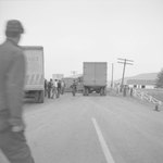 A group of men walking through and examining the tractor-trailer accident