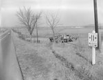A tractor-trailer accident in a field near a rural road with a road sign identifying the road as Route 11