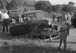 An automobile with a badly damaged front-end, and its passenger side door open. by William Garber