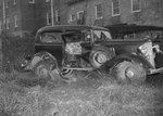 Side view of a damaged automobile that is parked behind a large building in an overgrown yard or field