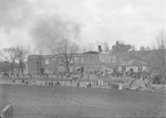 Distant view of a large building on fire, with a crowd of people gathered in front of it