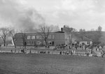 Distant view of a large building on fire, with a crowd of people gathered in front of it by William Garber
