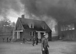 A young man pausing for a photograph, with a burning building in the background by William Garber