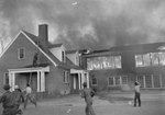 A large burning building, and a number of men running and working to stretch a water hose across the roof of a neighboring structure by William Garber