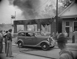 A burning building, with a car parked in front of it by William Garber